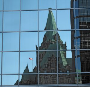 Government building reflected in glass building windows